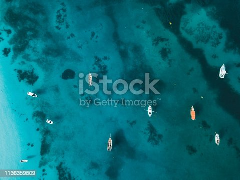 Aerial view on colorful boats anchored on the blue indian ocean of Zanzibar