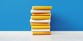 istock Colorful Books Sitting On Top Of Each Other In Front of Blue Wall 1168415132