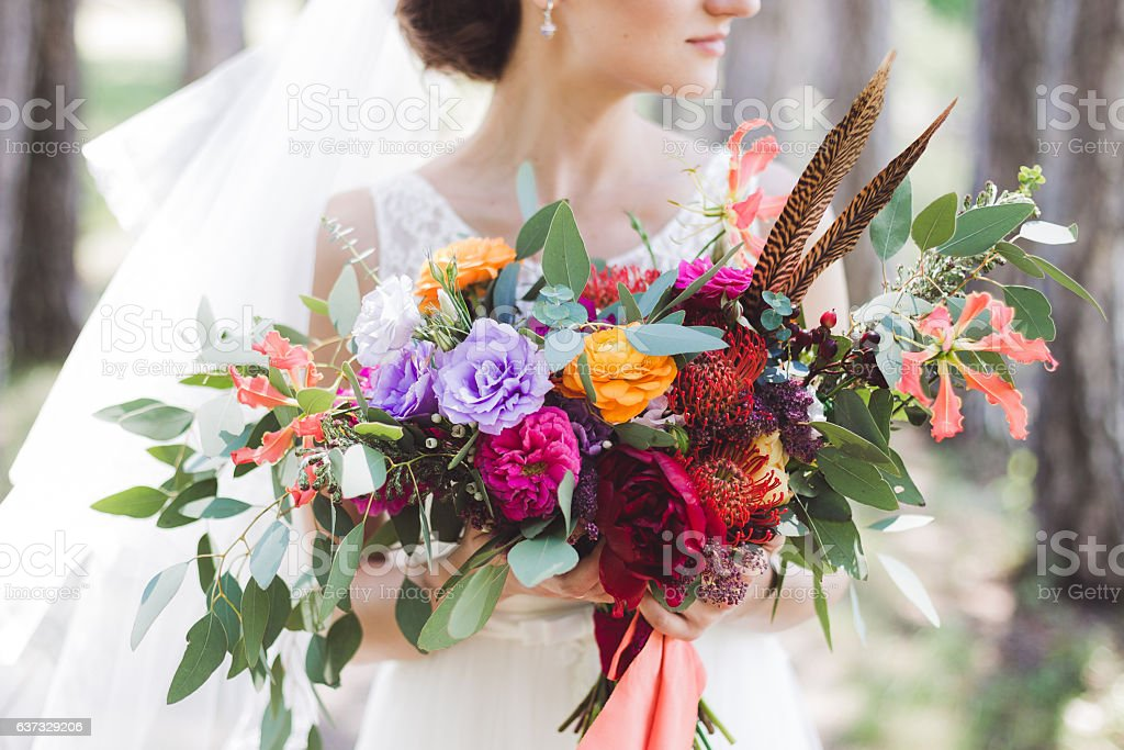 Colorful bouquet in boho style in the bride's hands stock photo