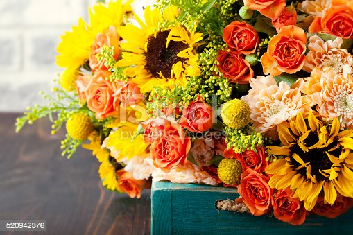 istock Colorful bouquet of flowers in turquoise box wooden table 520942376