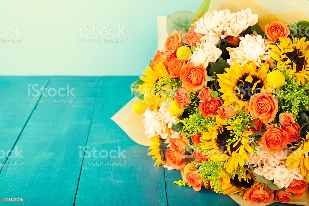 Colorful bouquet of flowers on turquoise wooden table Copy space