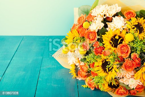 istock Colorful bouquet of flowers on turquoise wooden table Copy space 513807028