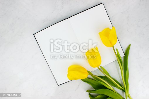Colorful bouquet of yellow tulips and sketchbook, notebook flat lay on marble background top view with copy space. Spring layout. Womans day, valentines day greeting. Banner template. Stock photo