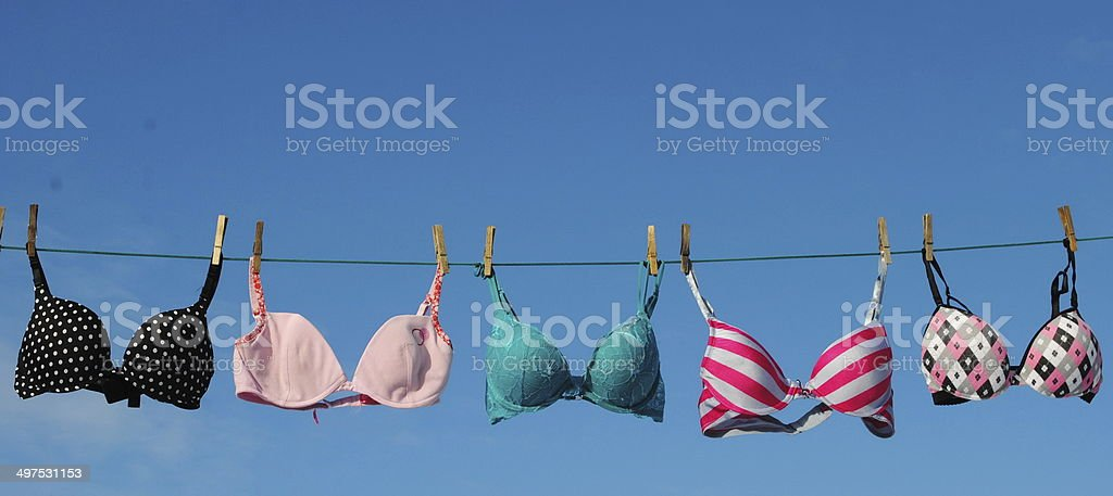 Colorful bras on clothesline stock photo