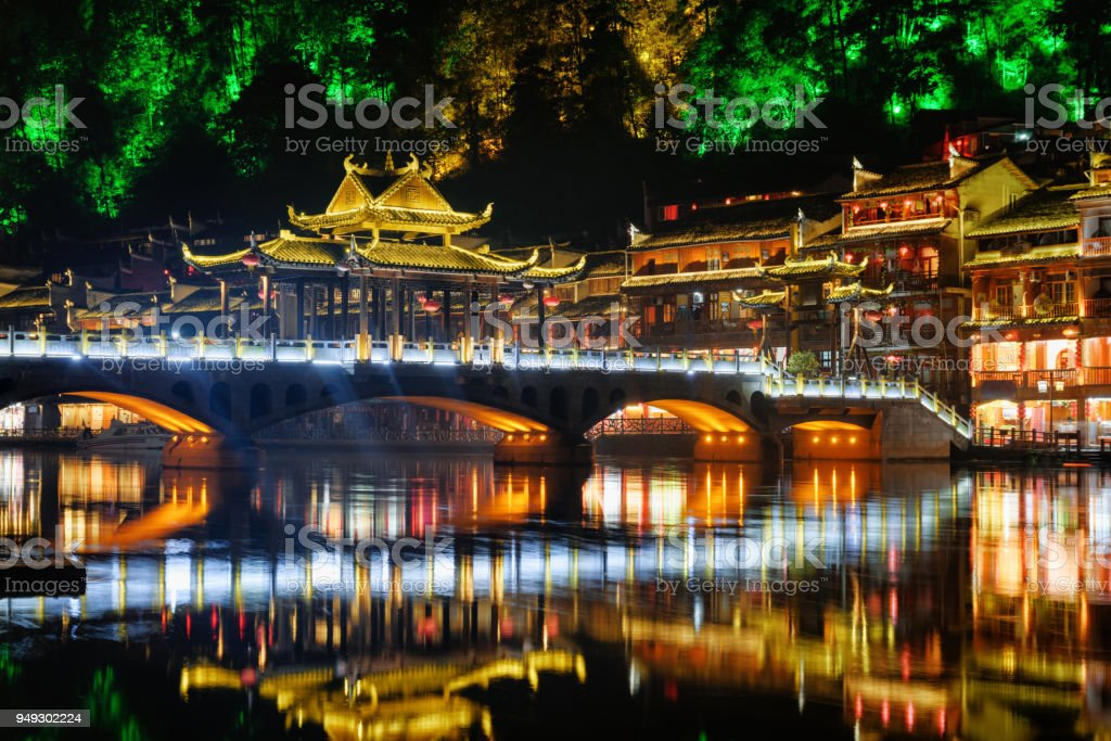 Colorful bridge reflected in water at night, Fenghuang stock photo