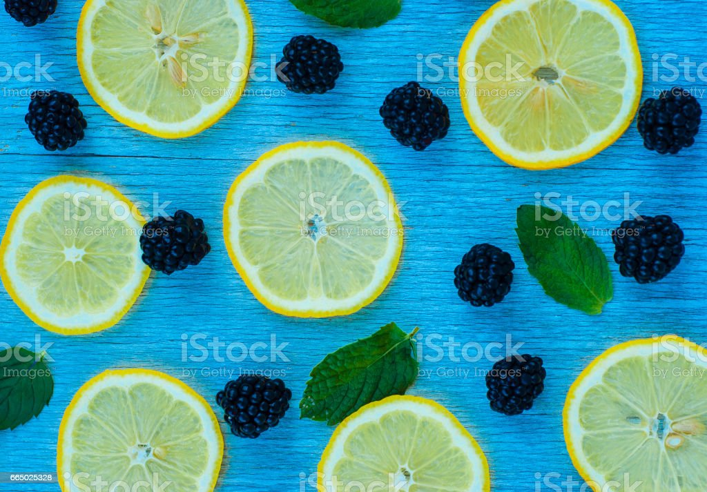Colorful bright pattern of leaves, blackberries and lemon on blue background stock photo