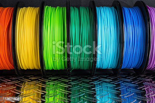 colorful bright row of spool 3d printer pla abs filament plastic material on dark black metal steel diamond plate background