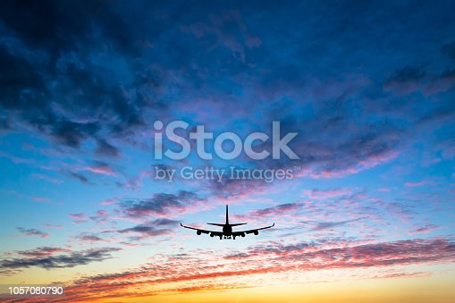 istock Colorful bright sunset with flying airplane silhouette 1057080790