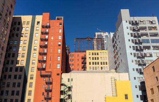 A group of buildings in Los Angeles, painted in a range of colors, against a deep blue sky.