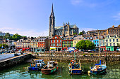 Colorful buildings, old boats and cathedral, Cobh harbor, County Cork, Ireland