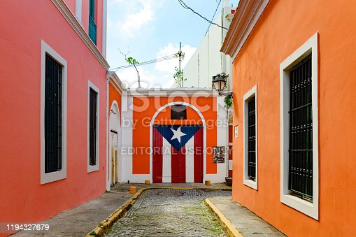 This is a color photograph of a Puerto Rican Flag on the exterior of a colorful building on Imperial Street in Old San Juan, Puerto Rico, USA.