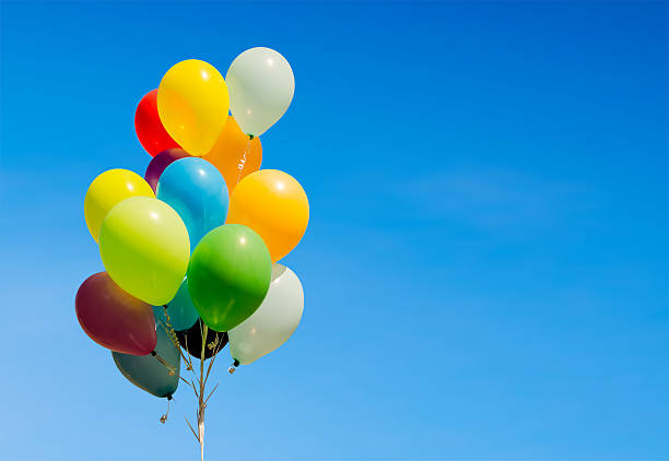 colorful bunch of helium balloons isolated on background stock photo