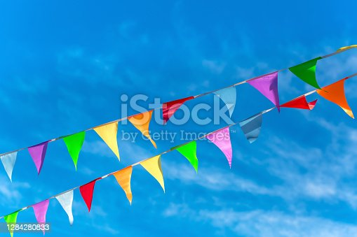 Colorful bunting flags in the wind. Festive background for holidays, anniversary, celebration. Multi-colored flag garland against a blue saturated sky