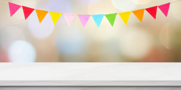 Colorful bunting party flags hanging on blur abstract bokeh light and white marble table background, birthday, greeting card background, banner, backgdrop, mock up, template, wallpaper stock photo