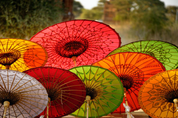 Colorful Burmese umbrellas sold in front of temple Beautiful parasols in souvenir shop in Myanmar. Hand made umbrellas are back lit, blurred trees and temple in background. myanmar stock pictures, royalty-free photos & images