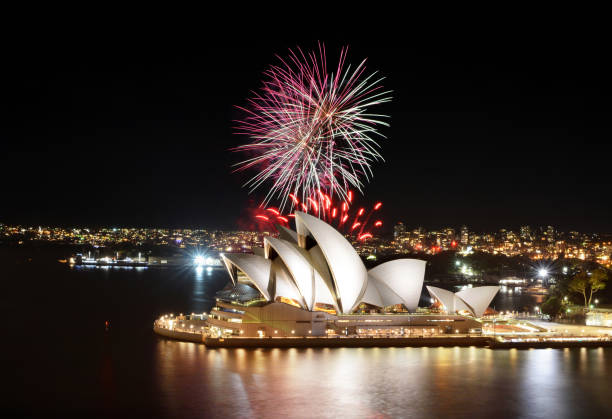 Colorful bursts of fireworks fill the night sky at the Sydney Opera House stock photo