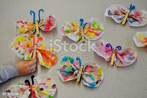 Funny and easy butterflies made from coffee filters, clothespins and chenille stems. ( Blurry child's hand holding and showing his project. )