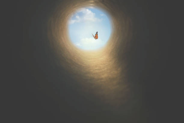 colorful butterfly finds its way out of a dark tunnel, concept of freedom stock photo