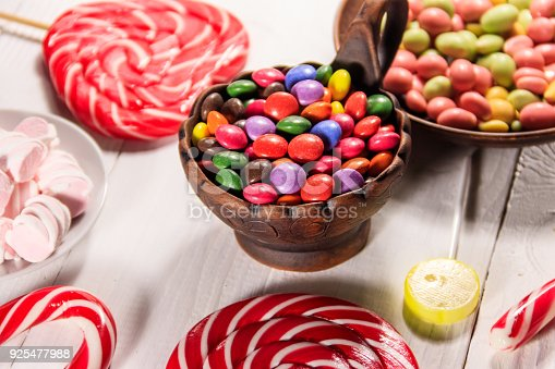 istock Colorful button shaped candies filled with chocolate in ceramic bowl on white wooden table 925477988