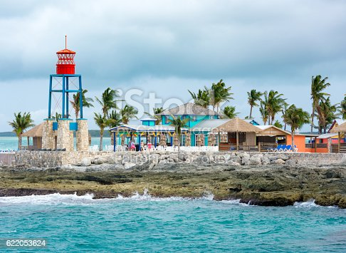 Coco Cay, BAHAMAS - October 16, 2016: Colorful cabins, tower, beach, and palm trees on a tropical Bahamas beach