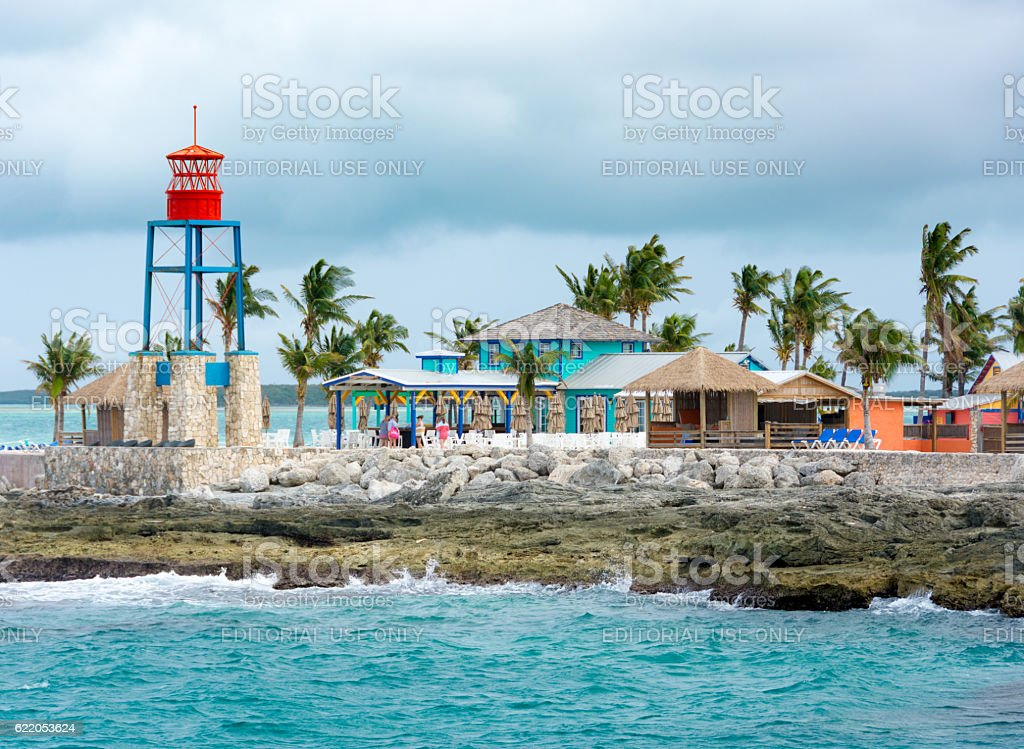 Colorful cabins, tower, palm trees and sand stock photo