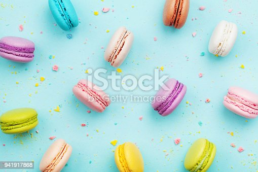 istock Colorful cake macaron or macaroon on turquoise pastel background from above. French almond cookies on dessert top view. 941917868