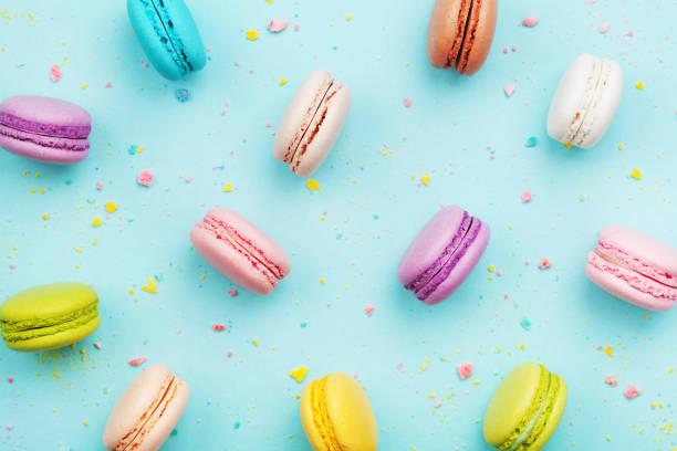 bolo colorido macaron ou macaroon em turquesa pastel fundo de cima. biscoitos de amêndoa francesas na sobremesa vista superior. - macaroon - fotografias e filmes do acervo