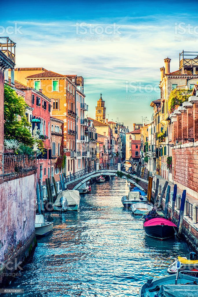 Colorful canal Venice with Boats and Church in Backgraund stock photo