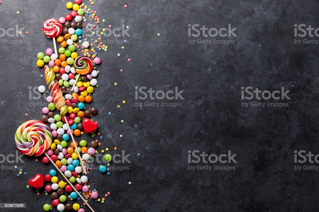 Colorful candies and lollipops over stone stock photo