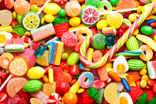 Top view of colorful candies, jellybeans and lollipops background. DSRL studio photo taken with Canon EOS 5D Mk II and Canon EF 100mm f/2.8L Macro IS USM