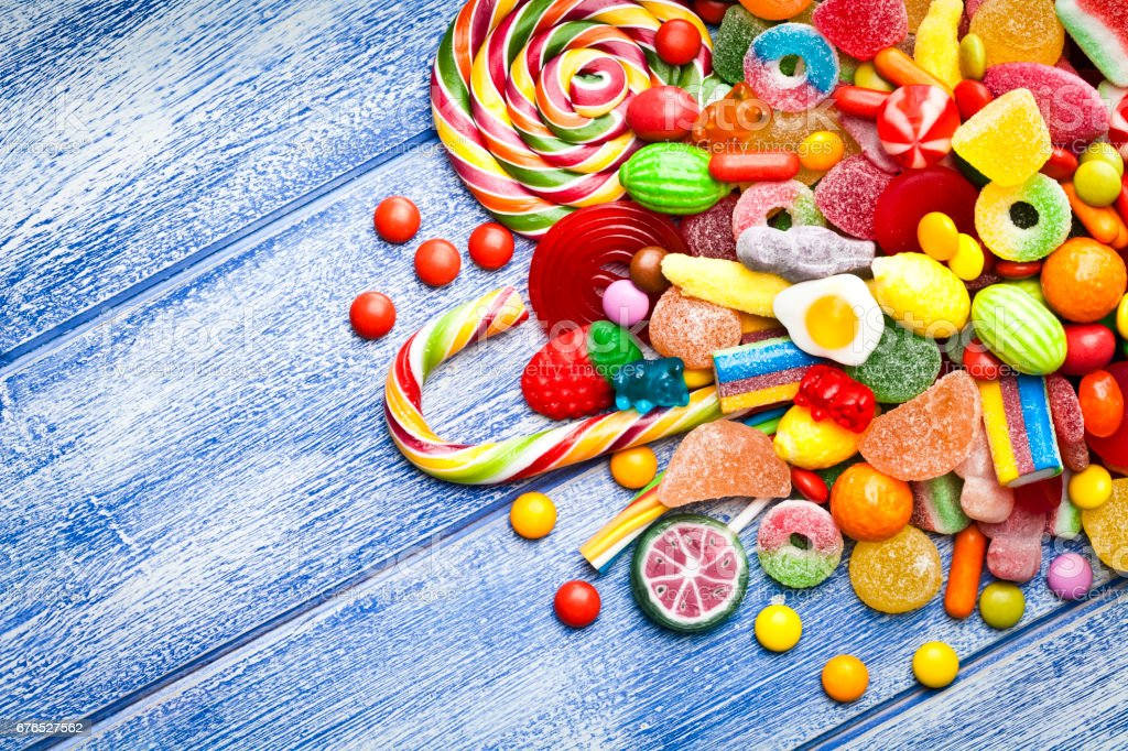 Colorful candies corner on blue table stock photo