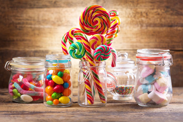 Colorful candies, jellies, lollipops, marshmallows and marmalade in a glass jars stock photo