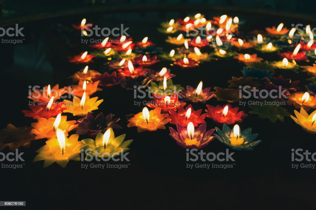 Colorful candle with fire on oil pool stock photo