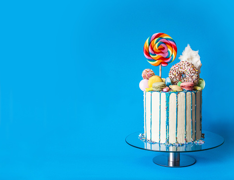 Colorful candy drip cake, blue background, right sided, with copy space. Perfectly usable for all party and fun projects.