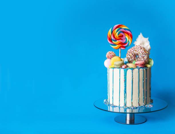 kleurrijke candy drip cake, blauwe achtergrond, rechts-zijdig, met kopieerruimte - genot stockfoto's en -beelden