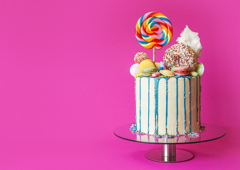 istock Colorful candy drip cake, pink background, right sided, with copy space 1158381662