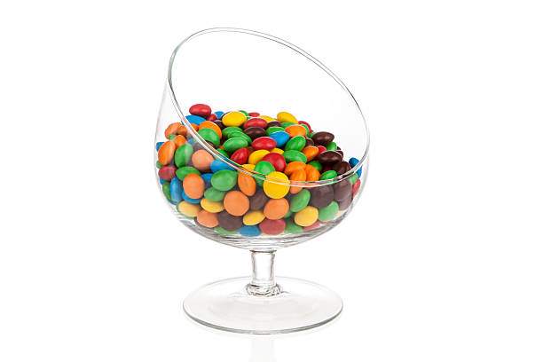 Colorful candy drops in glass isolated on white with reflection stock photo