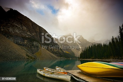 Colorful canoes at the dock on a rainy fall day, Moraine Lake, Valley of the Ten Peaks, Banff National Park.