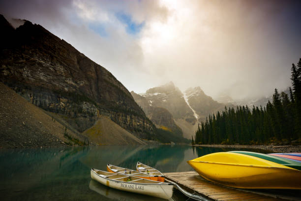 Colorful canoes in Moraine Lake Colorful canoes at the dock on a rainy fall day, Moraine Lake, Valley of the Ten Peaks, Banff National Park. valley of the ten peaks stock pictures, royalty-free photos & images