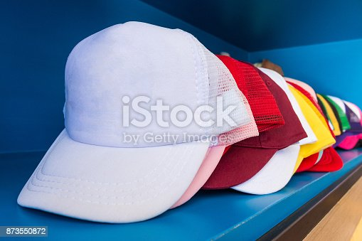 istock Colorful cap on blue shelf background. Fashion baseball or hiphop hat. 873550872