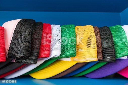 istock Colorful cap on blue shelf background. Fashion baseball or hiphop hat. 873550888