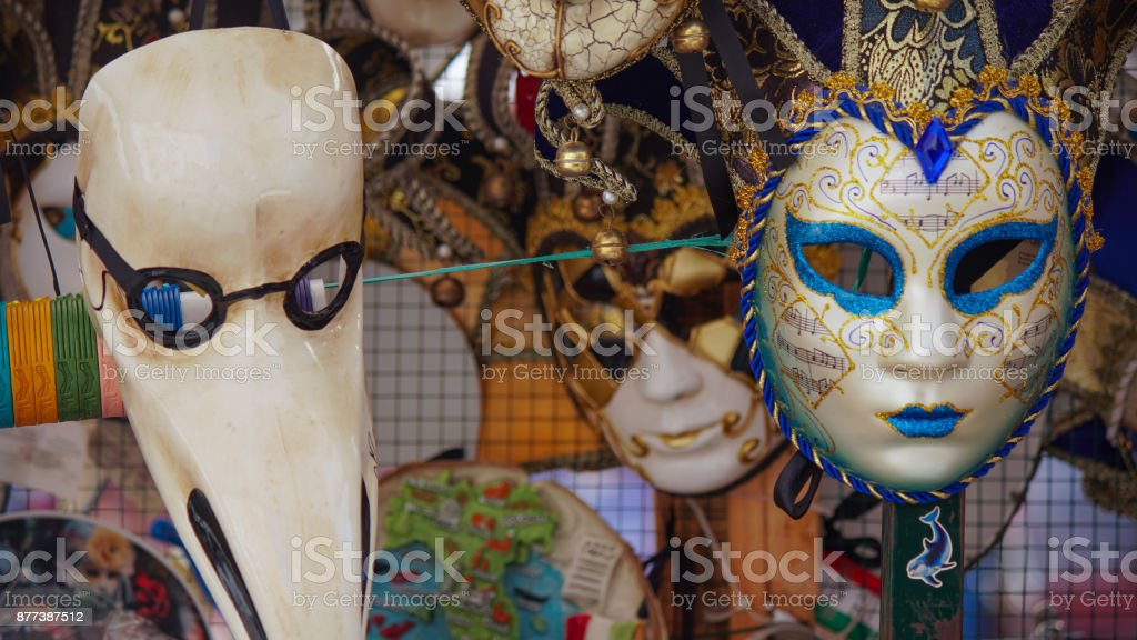 Colorful carnival masks on the market in Venice, Italy. Masks were worn in Venice to disguise the wearer from illicit activities:gambling, dancing, affairs or even political assignation. stock photo