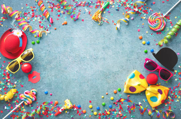 Colorful carnival or party background streamers and confetti and funny faces stock photo