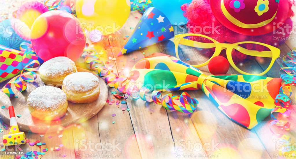 Colorful carnival or party background with donuts, balloons, streamers and confetti and funny face stock photo