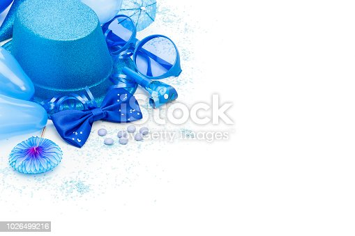 High angle view of blue colored carnival or party decoration items like streamers, party hats, bow ties, masquerade masks, pennants, party horn blowers  and confetti placed in a row at the top-left border of a white backdrop making a frame and leaving useful copy space for text and/or logo at the center-right. Predominant colors are blue and whiteHigh key DSRL studio photo taken with Canon EOS 5D Mk II and Canon EF 100mm f/2.8L Macro IS USM.