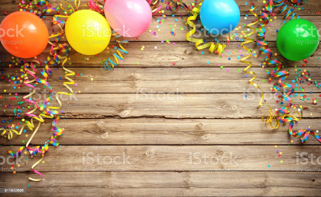 Colorful carnival or party frame of balloons, streamers and confetti on rustic wooden board royalty-free stock photo