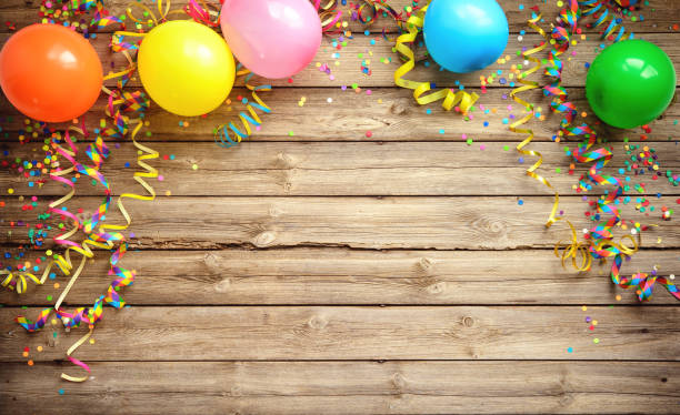 colorful carnival or party frame of balloons, streamers and confetti on rustic wooden board - anniversary stock photos and pictures
