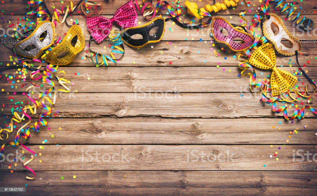 Colorful carnival or party frame of masks, streamers and confetti stock photo