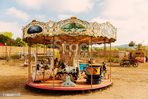 Colorful carousel standing on soil land, looking like abandoned.
