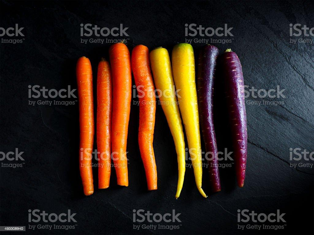 rainbow carrots on the black stone slate